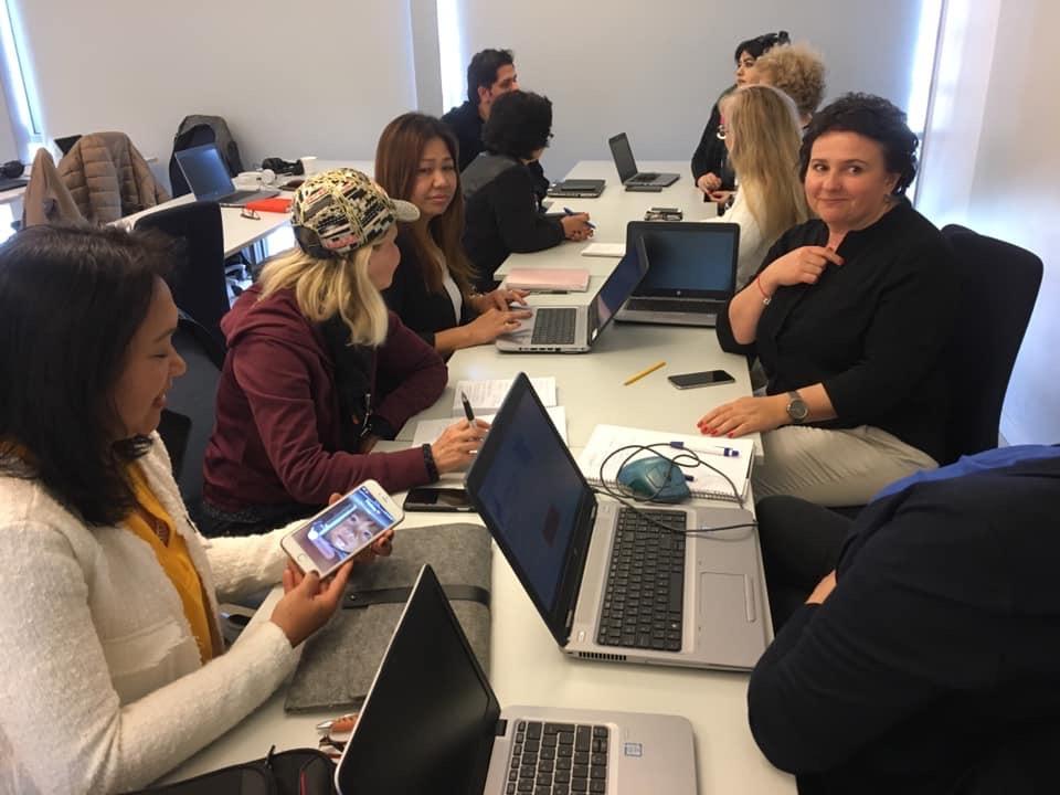 Deltager sitter och diskuterar och arbetar med digitala verktyg.